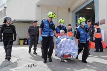 演練模擬﹕受傷的滋事在囚人在獄警押解下由消防人員送院治理