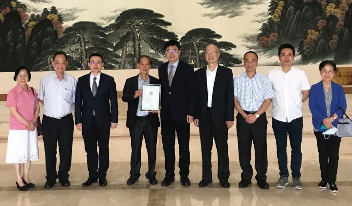 萬速成部長(右五)向關權昌(左四)頒發捐贈證書